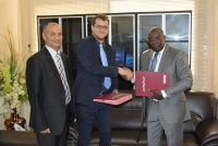 The Minister Paul Koffi Koffi and the IIEP-Pôle de Dakar Coordinator Guillaume Husson exchange copies of the signed agreement, with Naceur Chraïti, Head of PEFOP